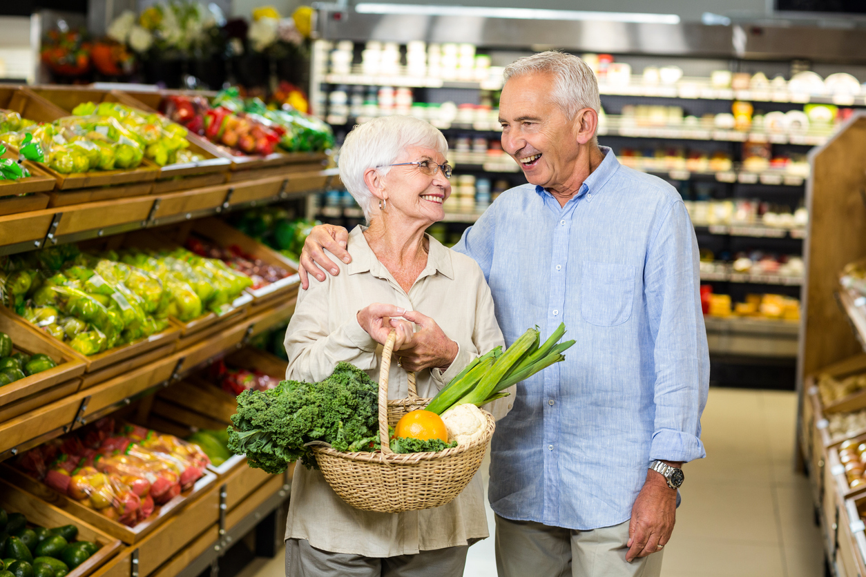 Smiling senior couple holding basket with vegetables
